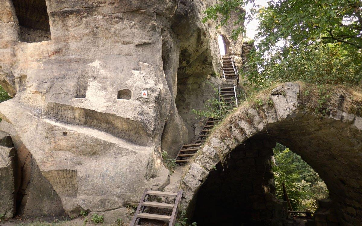 Právě z rozvalin hradu Skály podle románu vycházelo tajuplné světlo vzbuzující zvědavost i bázeň kolemjdoucích. Dnes se však vyplatí sem vyšplhat spíše kvůli skvělému panoramatickému výhledu na Broumovsko, Ostaš, ale i polské Stolové hory. Z hradu, jehož jádrem byla mohutná skalní věž, zbyly dnes již pouze zbytky klenutého sklepa, studny a několik místností vytesaných do skal. | © Marie Hochmanová