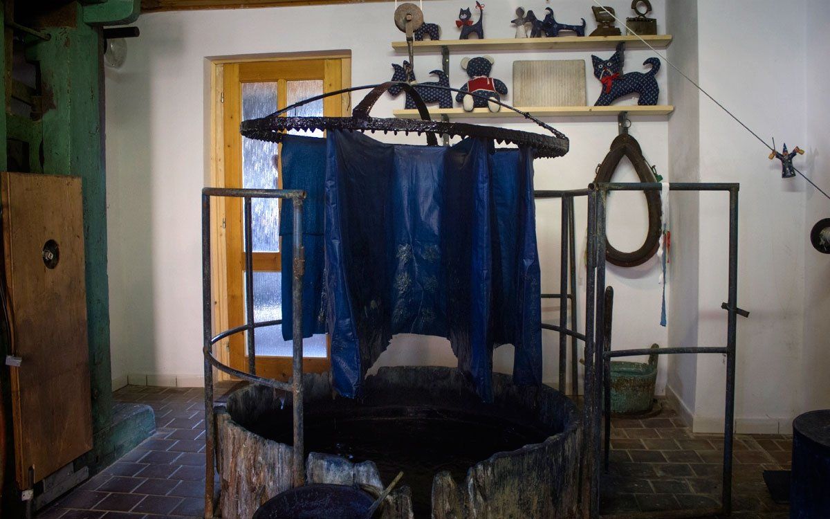 Po zaschnutí krycí vrstvy se látka připevní na barvířskou korunu a ponoří se do temné modři zvané indigo, pak se nechá chvíli na vzduchu oxidovat a celý proces se několikrát opakuje. | © Jaro Dufek