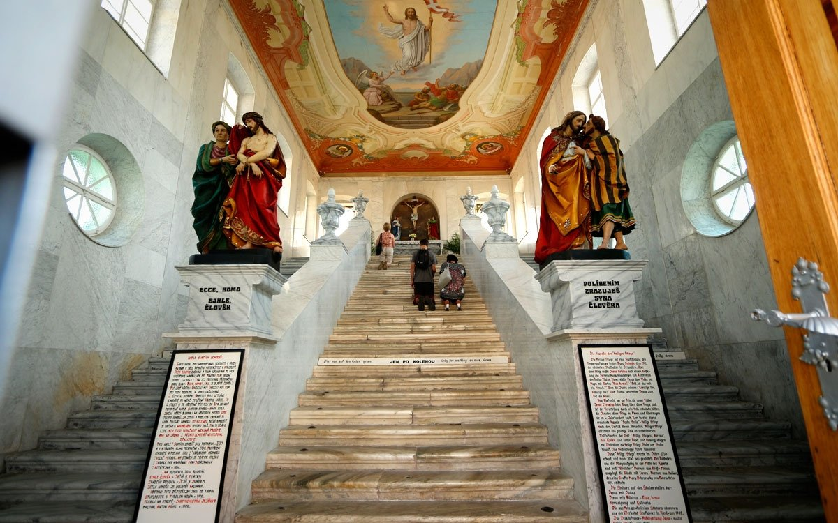 Uvnitř nádvoří Poutníků, uprostřed kláštera, byla v roce 1710 postavena unikátní kaple, která je kopií schodiště v hradu Antonia v Jeruzalémě, po němž kráčel Ježíš Kristus k soudnímu stolci Piláta. Do schodů ozdobených barokními sochami s biblickými motivy mají modlící se poutníci vylézt po kolenou, dolů se sestupuje bočním schodištěm. | © sius