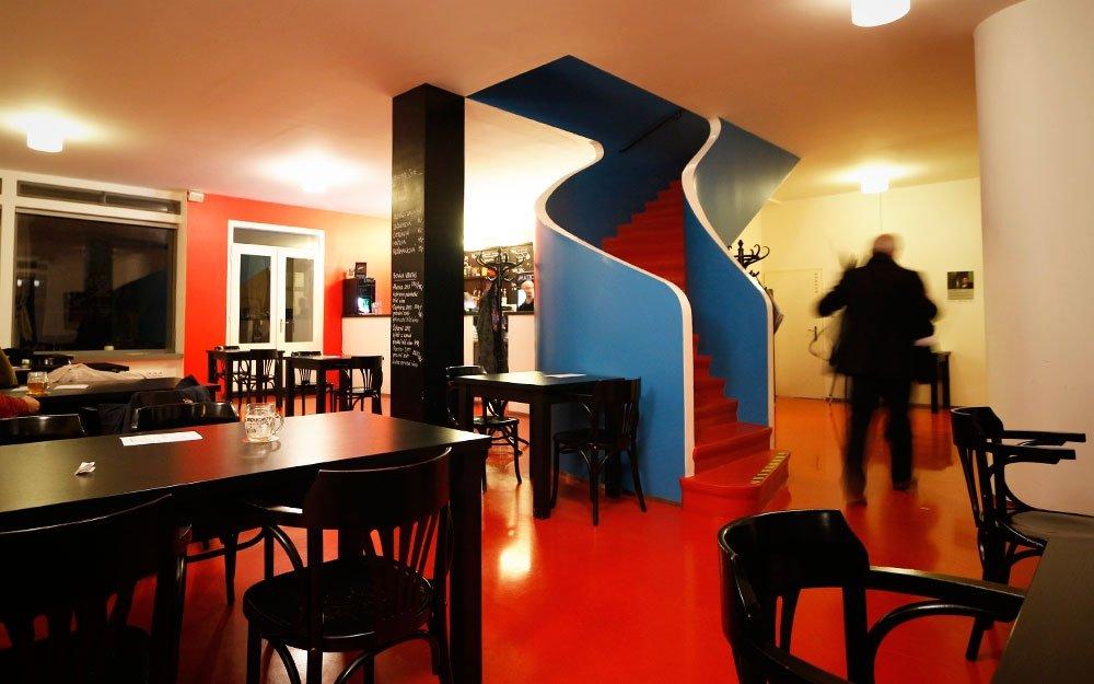 Mladý začínající architekt Josef Kranz navrhl v roce 1927 puristicky čistou budovu, která v sobě spojuje kavárnu a privátní prostory bytu majitele. Čisté, ale dynamické křivky schodiště, výrazné, lesklé, olejové barvy, dokonale vyvážené lidské měřítko a uliční průčelí redukované natolik, že působí téměř jako plakátová plocha, se spojily do unikátního celku, který je již od od konce 70. let zapsaný do Státního seznamu nemovitých kulturních památek. | © sius