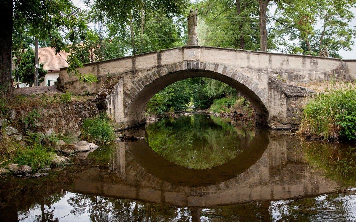 Vodní hamr není jedinou technickou památkou v Dobřívi. Kamenný most ze 14. století, nazývaný švédský, kdysi spojoval obec se starým hamrem a své jméno prý dostal podle přepravy dělostřeleckých koulí z hamru, kde se odlévaly. | © Eva Kořínková