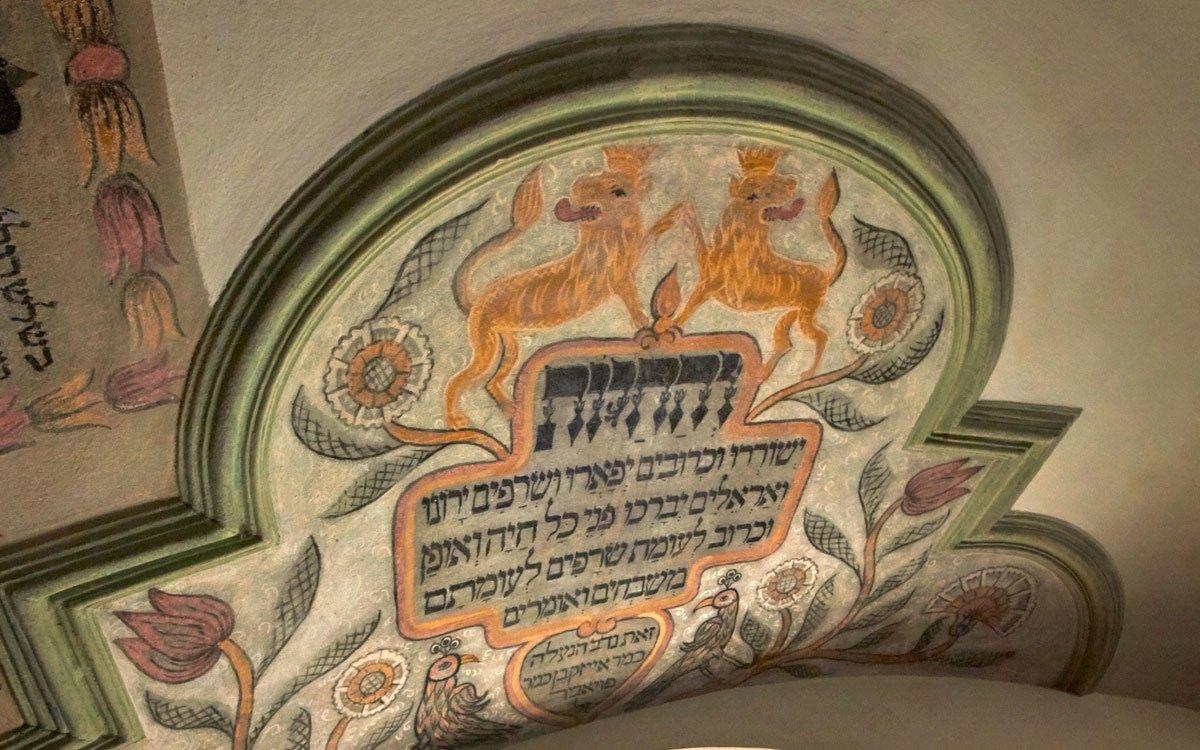Na rozdíl od ostatních židovských modliteben postavených v tomto stylu se holešovské synagoze vyhnulo nacistické plenění, a dochovala se tak vtéměř nezměněné podobě. Paradoxně ji přitom zachránil její nepříliš utěšený stav i to, že vzácnou vnitřní výzdobu postupem času překryla hrubá omítka. Teprve na přelomu 50. a 60. let minulého století pod ní místní zedník Jiří Hanák objevil původní malby, trvalo však více než deset let, než se synagoga po celkové rekonstrukci dočkala svého znovuotevření. | © Jaro Dufek