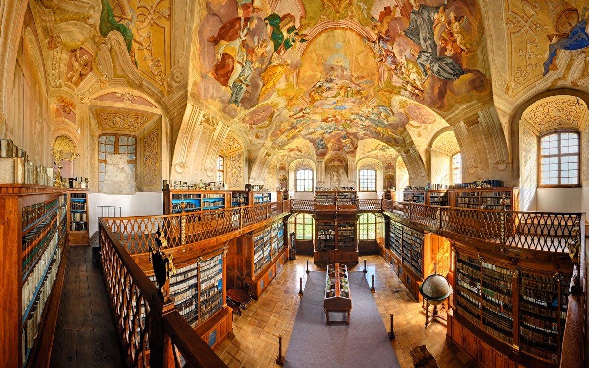 Dávnou románskou a gotickou tvář knihovny i kláštera překryla v 18. století velkorysá přestavba podle plánů architekta Jana Blažeje Santini-Aichela. A kromě nádherné výzdoby je tu ještě jeden důvod, proč benediktinský klášter navštívit. Pokud se hodláte vydat na Svatojakubskou cestou do španělského Santiaga de Compostela, v Rajhradu se můžete připojit k jedné z větví – razítko do poutnického průkazu dostanete právě v klášteře. | © Libor Sváček, archiv CzechTourism