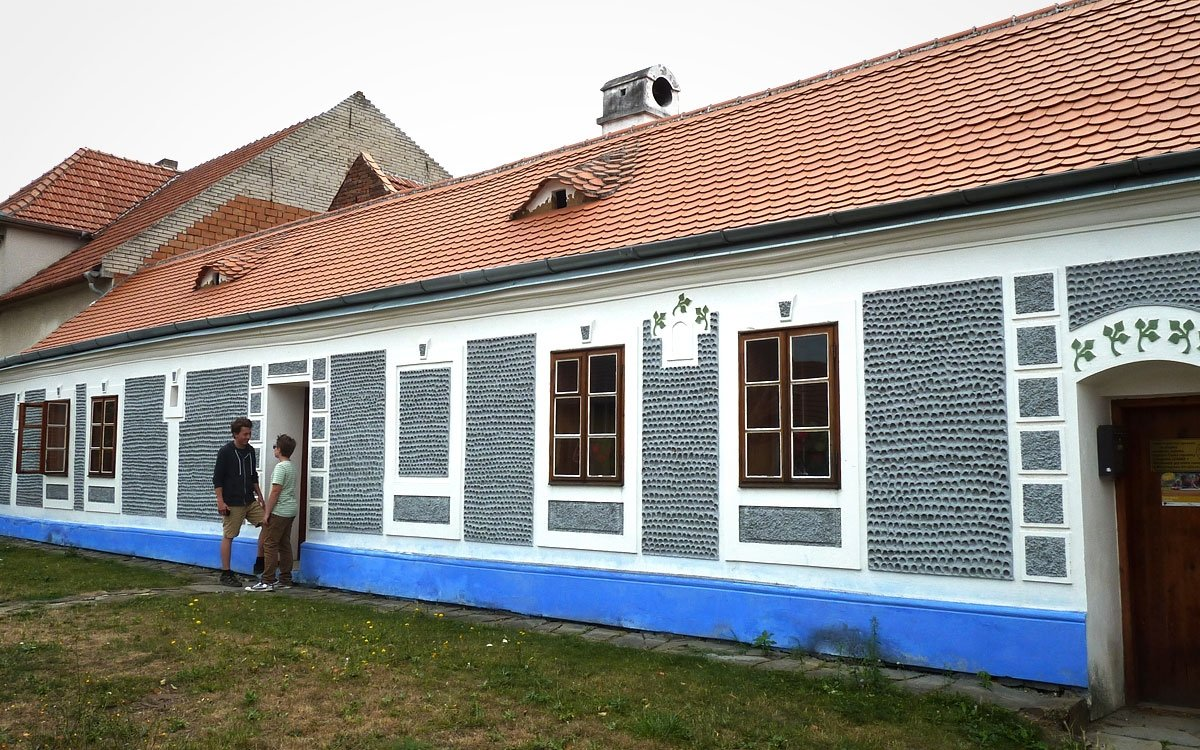 Moravský malíř a grafik, představitel romantického historismu a secesního dekorativismu Joža Uprka se narodil 26. října 1861 v tomto malém domku v Kněždubu. Nedaleko rodné obce  v Hroznové Lhotě pak v roce 1904 koupil malý domek a nechal jej přestavět podle návrhu architekta Dušana Jurkoviče na patrovou vilu s dřevěnými prvky, inspirovanou lidovou architekturou. Hostil zde řadu osobnosti ze světa kultury jako například bratry Mrštíky, Zdenku Braunerovou, Herberta Masaryka, Leoše Janáčka, Vítězslava Nováka či Augusta Rodina. | © Jitka Slavíčková