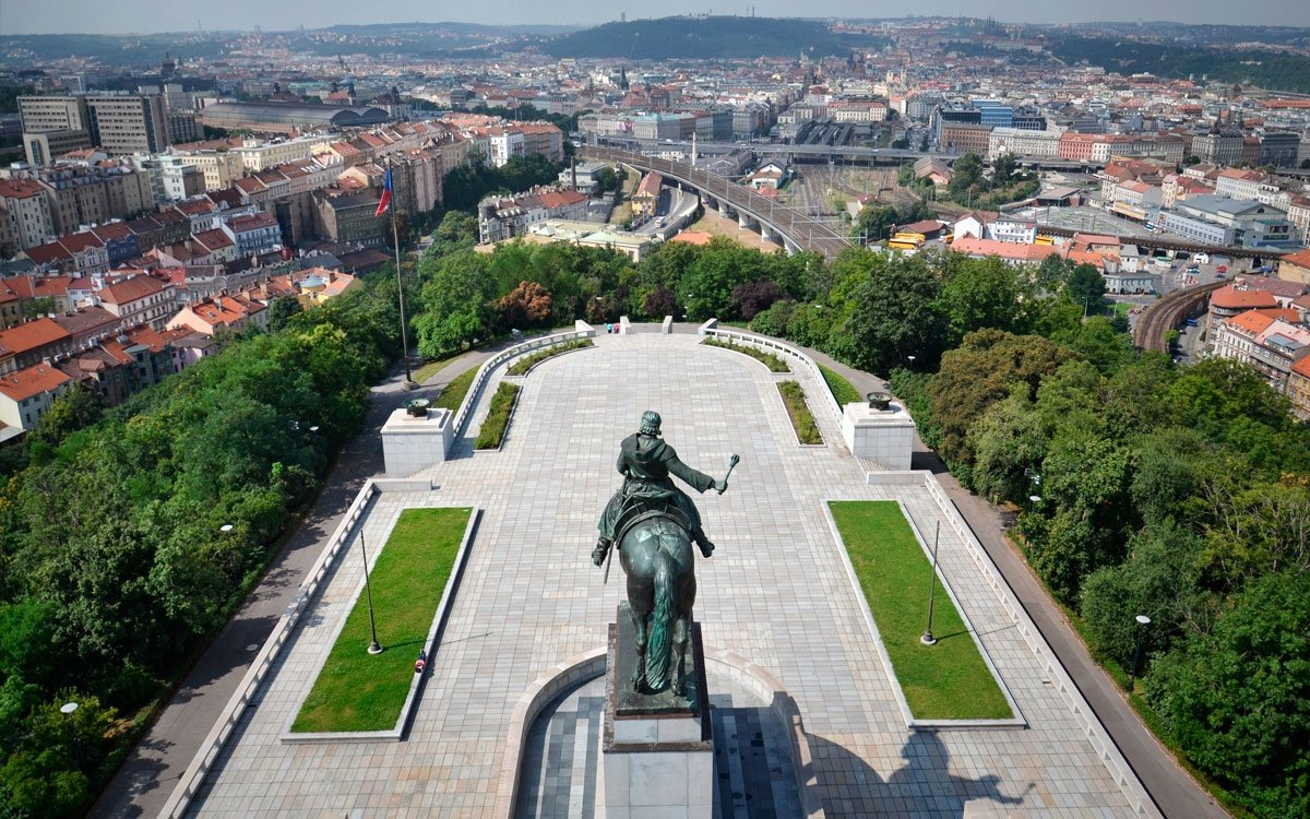 """Chcete-li pokračovat v procházce metropolí na téma """"Praha monumentální"""", další zajímavou zastávkou může být Národní památník na Vítkově. Funkcionalistický památník snekropolí a jednou z největších bronzových jezdeckých soch na světě byl dokončen nedlouho před vypuknutím druhé světové války a budova začala sloužit jako skladiště německého wehrmachtu. Po válce komunistický režim v útrobách památníku pohřbíval významné představitele strany a devět lez zde bylo dokonce vystaveno mumifikované tělo Klementa Gottwalda. Dnes je v rekonstruovaném památníku historická expozice a na střeše objektu kavárna s úžasným výhledem na Prahu."""