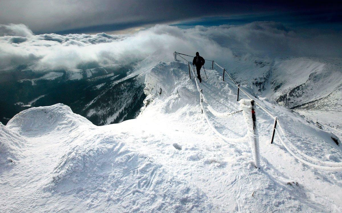 """Krakonošovy sněhové nadílky jsou stejně bohaté jako mlha, kterou vypouští ze své fajfky. Pohled z vrcholu Sněžky je tak díky oblakům, valícím se většinou pod vrcholem naší nejvyšší hory, neméně impozantní, i když zrovna není populární """"azuro"""", nebo jak by řekli Homolkovi """"Jadran"""".   © Dreamstime"""